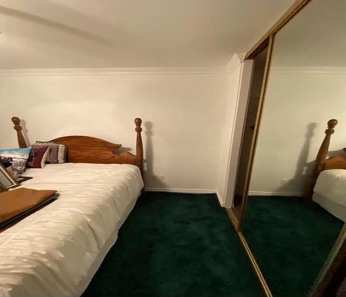 white walls, green carpet bed in center of room