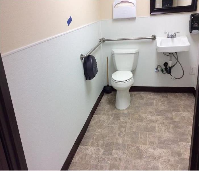 Commercial Public restroom flooded, white walls with blue tape marks walls that are wet